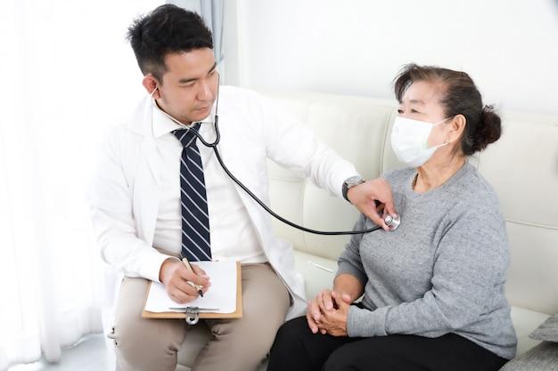 Joven médico asiático hablando con una mujer mayor en el hospital Foto Premium