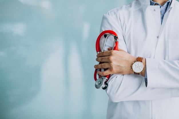 Joven médico guapo en una túnica médica con estetoscopio Foto gratis