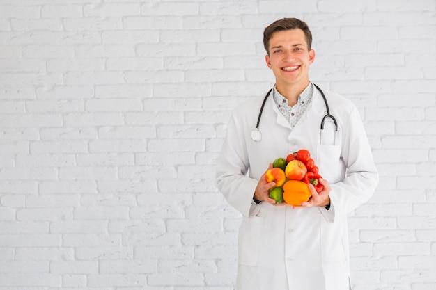 Joven médico masculino de pie contra la pared con alimentos saludables Foto gratis