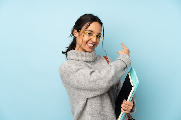 Joven mestiza mujer yendo a la escuela en la pared azul apuntando hacia atrás Foto Premium