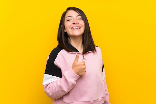Joven mexicana sobre amarillo aislado dando un pulgar arriba gesto Foto Premium