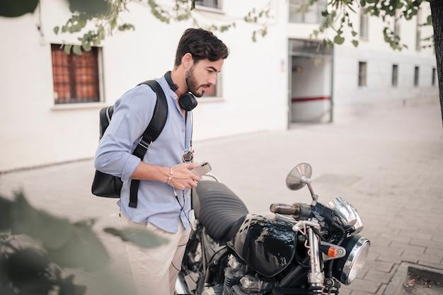 Joven mirando en un espejo de moto Foto gratis