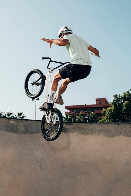 Joven montando en una bicicleta bmx en skatepark Foto gratis