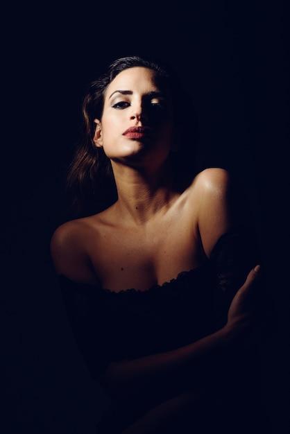 Joven morena en lencería negra en iluminación de claroscuro. Foto gratis