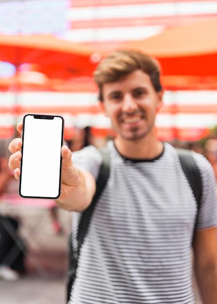 Joven mostrando una pantalla de teléfono inteligente Foto gratis