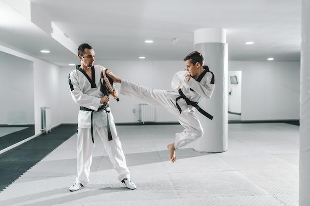Joven muchacho caucásico en dobok pateando descalzo mientras el entrenador sostiene el objetivo de la patada. concepto de entrenamiento de taekwondo. Foto Premium