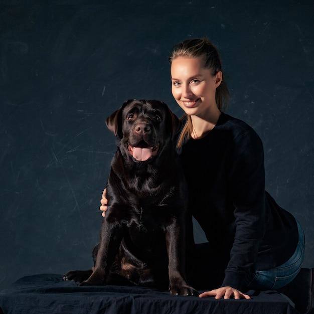 La joven mujer abrazando a un perro de raza mix Foto gratis