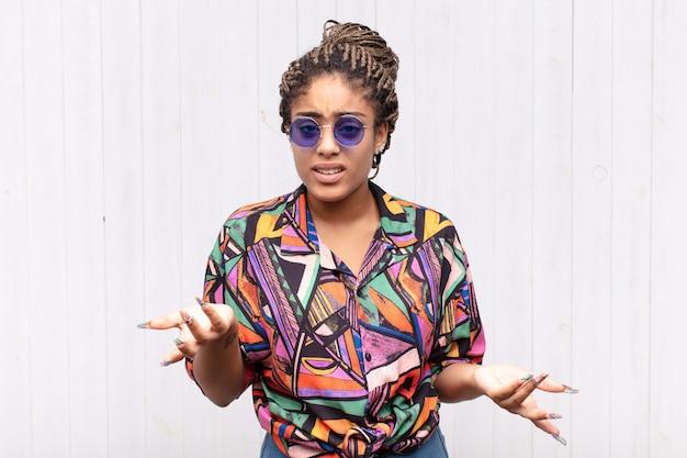 Joven mujer afro que se siente despistada y confundida, sin saber qué opción u opción elegir, preguntándose Foto Premium