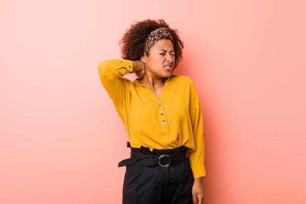 Joven mujer afroamericana contra un fondo rosa sufriendo dolor de cuello debido al estilo de vida sedentario. Foto Premium