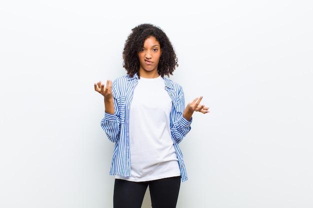 Joven mujer afroamericana fresca que se siente desorientada y confundida, sin saber qué opción u opción elegir, preguntándose Foto Premium