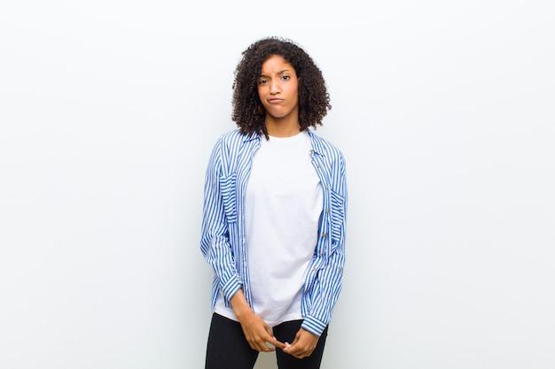 Joven mujer afroamericana fresca sintiéndose confundida y dudosa, preguntándose o tratando de elegir Foto Premium