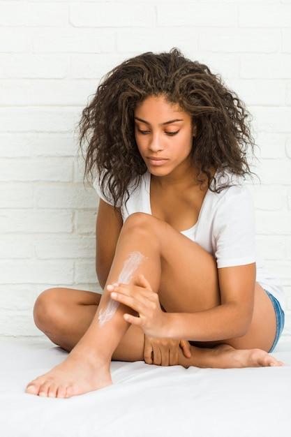 Joven mujer afroamericana obtener crema hidratante en las piernas Foto Premium