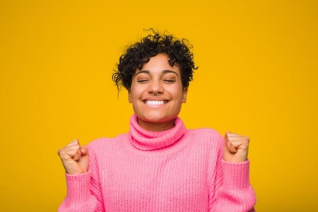 Joven mujer afroamericana con un suéter rosa levantando el puño, sintiéndose feliz y exitoso. concepto de victoria Foto Premium