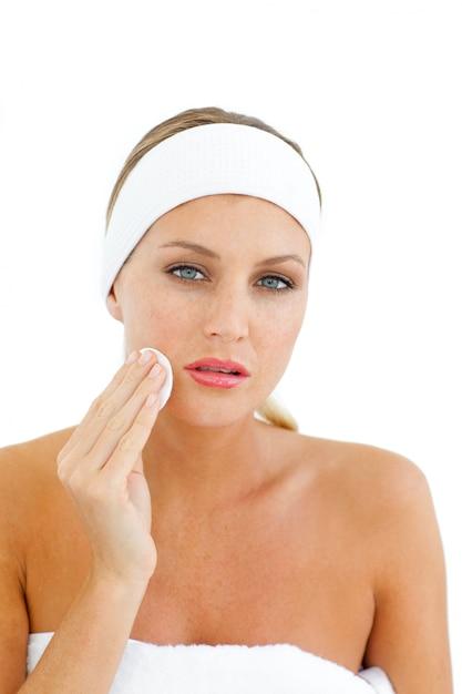 Joven mujer aplicando una base de maquillaje Foto Premium