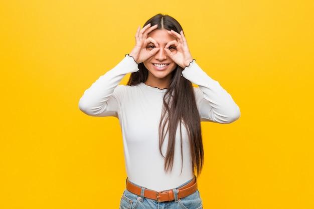 Joven mujer árabe bonita contra un amarillo que muestra signo bien sobre los ojos Foto Premium