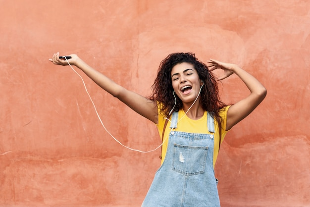 Joven mujer árabe escuchando música con auriculares al aire libre Foto Premium
