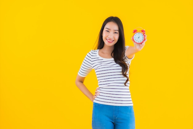 Joven mujer asiática mostrar reloj o alarma Foto gratis