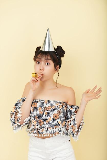 Joven mujer asiática posando en estudio con sombrero de fiesta y con matraca Foto gratis