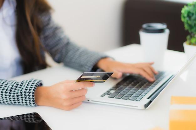 Joven mujer asiática con tarjeta de crédito con laptop para compras en línea Foto gratis