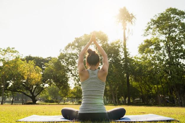 Joven mujer asiática de yoga al aire libre mantiene la calma y medita mientras practica yoga Foto gratis