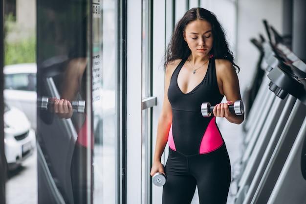 Joven mujer atractiva en el gimnasio con pesas Foto gratis