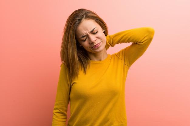Joven mujer bastante joven que sufre dolor de cuello debido al estilo de vida sedentario. Foto Premium