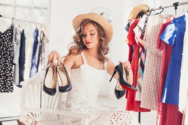 La joven mujer bonita eligiendo y probándose zapatos modelo en la tienda Foto gratis