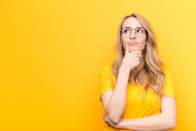Joven mujer bonita rubia pensando, sintiéndose dudosa y confundida, con diferentes opciones, preguntándose qué decisión tomar contra la pared de color Foto Premium