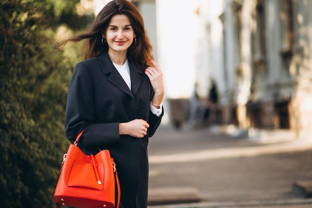 Joven mujer hermosa en la chaqueta roja de moda y bolso rojo caminando en el parque de otoño