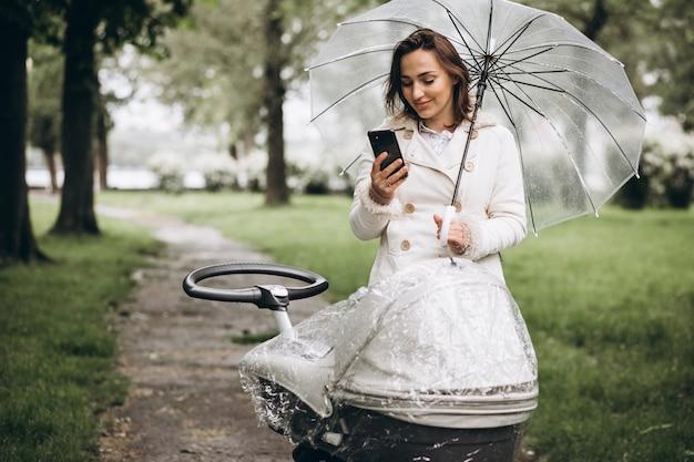 Joven mujer caminando con carro de bebé bajo el paraguas en un clima lluvioso Foto gratis