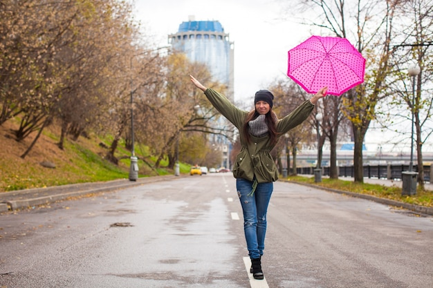 Joven mujer caminando con paraguas en otoño día lluvioso Foto Premium