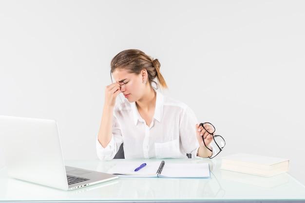 Joven mujer cansada delante de una computadora portátil en el escritorio de oficina, aislado sobre fondo blanco. Foto gratis