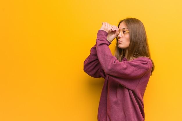 Joven mujer casual haciendo el gesto de un catalejo Foto Premium