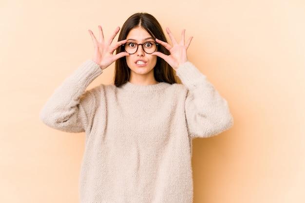Joven mujer caucásica en pared beige manteniendo los ojos abiertos Foto Premium