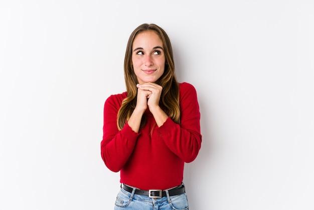 Joven mujer caucásica posando aislada mantiene las manos debajo de la barbilla, está mirando felizmente a un lado. Foto Premium