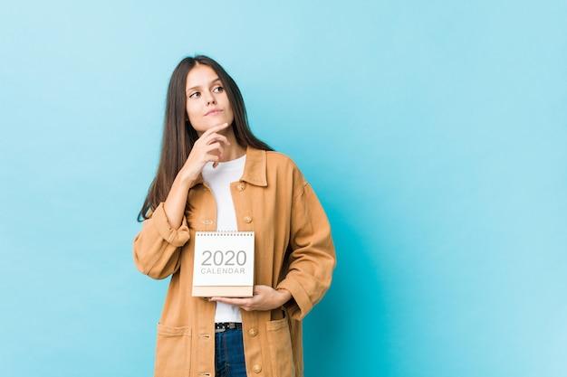 Joven mujer caucásica sosteniendo un calendario 2020 mirando hacia los lados con expresión dudosa y escéptica. Foto Premium