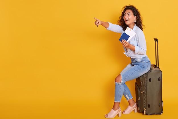 Joven mujer caucásica, vestida con ropa casual, con pasaporte con boletos aéreos mientras está sentado en la maleta Foto gratis