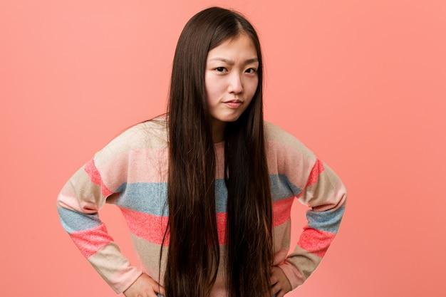 Joven mujer china fresca regañando a alguien muy enojado. Foto Premium