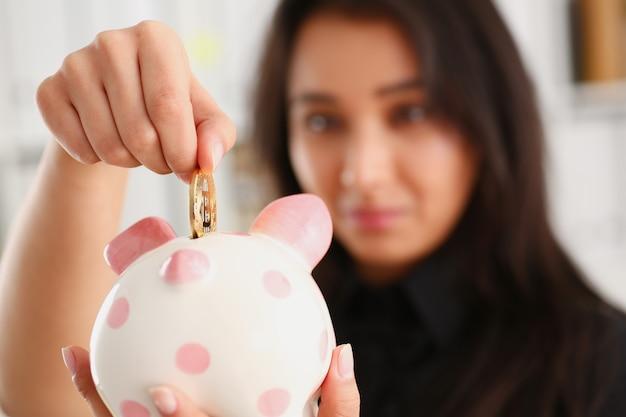 Una joven mujer china sonriente que sostiene la moneda bitcoin en su mano la empuja en forma de hucha de tema de almacenamiento de ahorro de hucha rosa en moneda criptográfica. Foto Premium