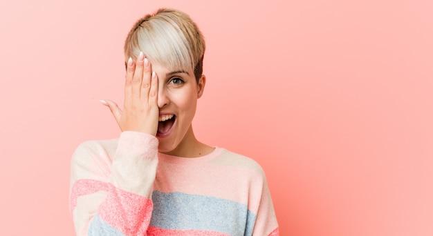 Joven mujer con curvas naturales divirtiéndose cubriendo la mitad de la cara con la palma. Foto Premium
