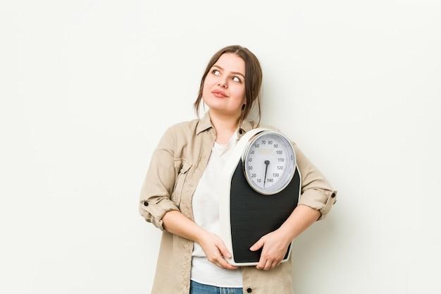 Joven mujer con curvas sosteniendo una escala soñando con lograr objetivos y propósitos Foto Premium