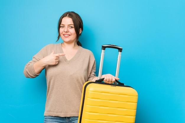 Joven mujer con curvas sosteniendo una maleta sonriendo y apuntando a un lado, mostrando algo en el espacio en blanco. Foto Premium