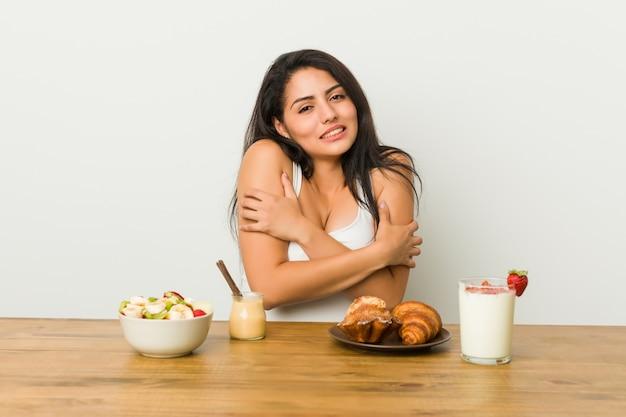 Joven mujer con curvas tomando un desayuno frío debido a la baja temperatura o una enfermedad. Foto Premium