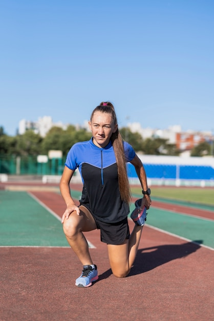 Joven mujer deportiva estiramiento en el estadio Foto gratis