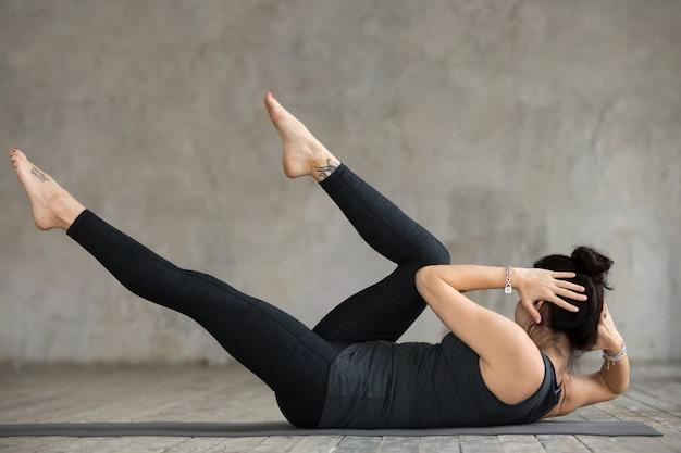 Joven mujer deportiva haciendo ejercicio entrecruzado Foto gratis