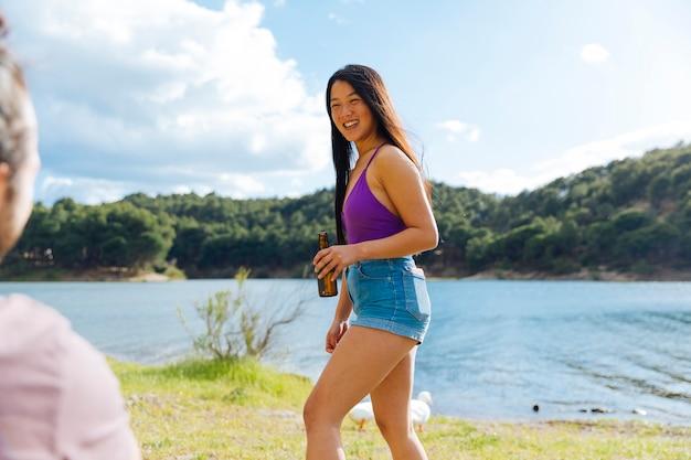 Joven mujer descansando en la orilla del río Foto gratis