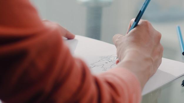 Joven mujer embarazada asiática dibujo bebé en el vientre y la familia en el cuaderno. mamá se siente feliz sonriendo positiva y pacífica mientras cuida al niño en la mesa en la sala de estar en casa. Foto gratis