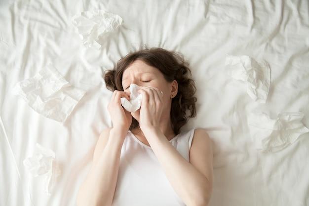 Joven mujer estornudo en el tejido Foto gratis