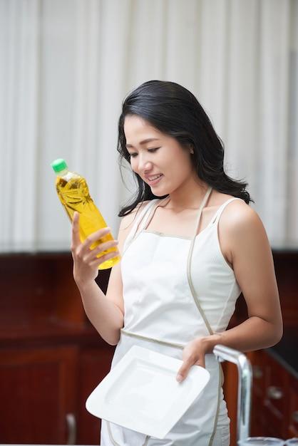 Joven mujer étnica con botella de detergente en casa Foto gratis