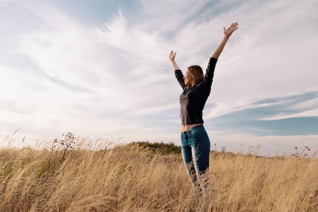 Joven mujer feliz en un campo de oro en puesta de sol. Foto gratis